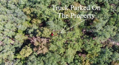 The truck is in the center of the photo and is parked on the property