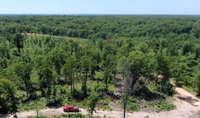 Aerial facing westerly over the property with the truck parked on the easement road just off of the county road.
