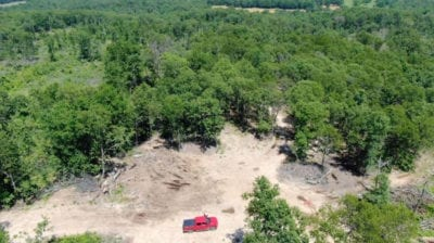 Aerial looking down at the open area on the west side of the property.