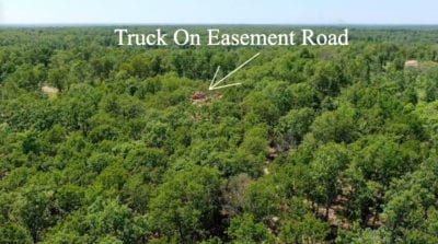 Aerial over the middle looking west with the truck parked on the easement road in the distance.
