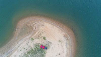 Aerial photo of the truck parked on beach.