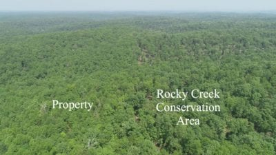 Aerial facing north on the east side of the property with the land on the left and the Conservation Land on the right.